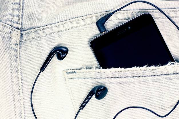 Closeup to jeans pocket with smartphone and headphones
