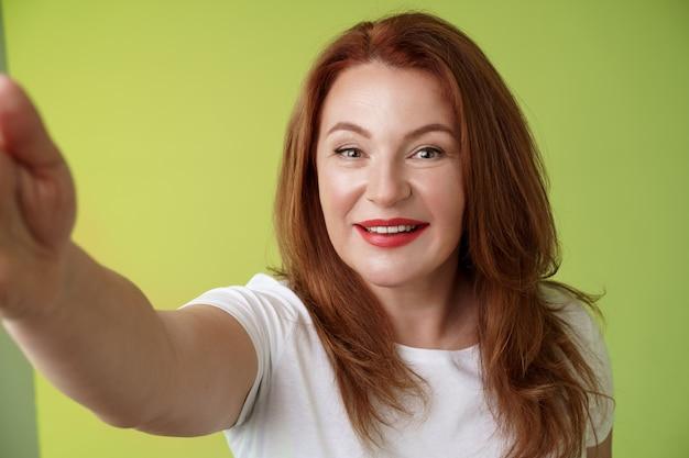 근접 촬영 즐거운 열정적 인 빨간 머리 매혹적인 중년 여성은 셀카를 찍는 카메라를 향해 팔을 뻗어 ...