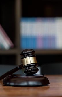 背景がぼやけている暗い部屋の木製のテーブルにクローズアップ裁判官のガベル。法律の概念。垂直方向のビュー。