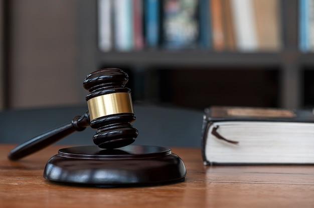 背景がぼやけている暗い部屋の木製のテーブルにクローズアップ裁判官のガベル。法律の概念。