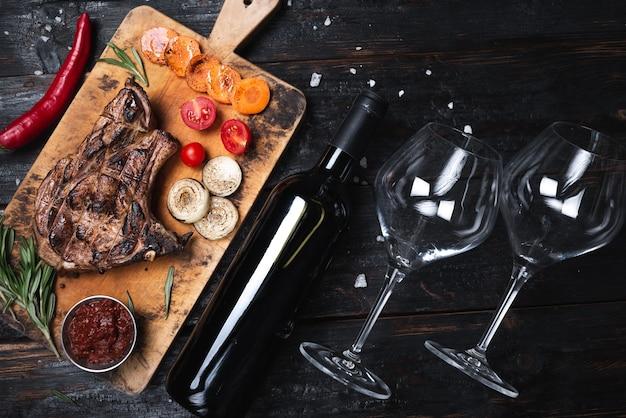 Сочный стейк крупным планом лежит на разделочной доске, мясо на гриле. бутылка сухого вина и два стакана. ужин на двоих, меню ресторана