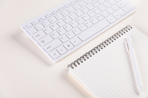 Closeup of a keypad and a notepad with pen on a white table - concept of job