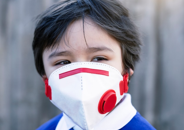 Closeup kid  face wearing protectve face mask for pullution or virus