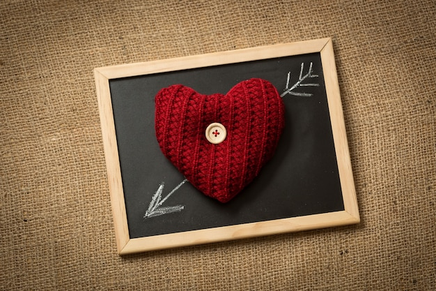 Closeup of knitted heart lying on blackboard with drawn arrow