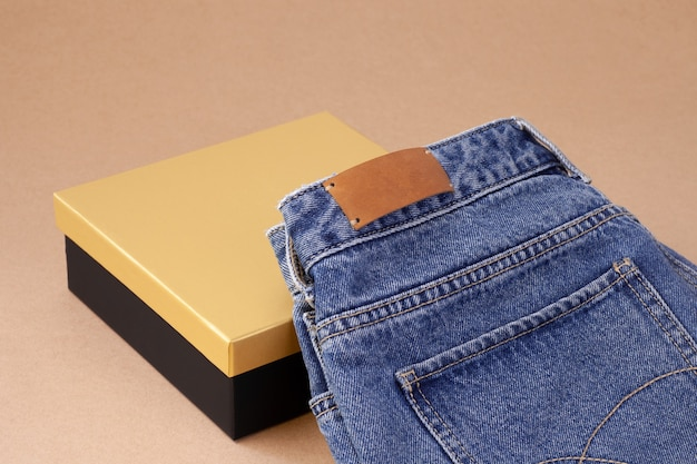 Closeup leather empty tag or label on the back pocket of blue jeans on a vase of spool yarn with black golden box