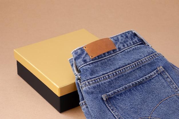 Кожаная пустая бирка крупным планом или этикетка на заднем кармане синих джинсов на вазе из катушечной пряжи с черной золотой коробкой