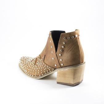 Primo piano della scarpa marrone femminile a tacco alto in pelle decorata con parti metalliche