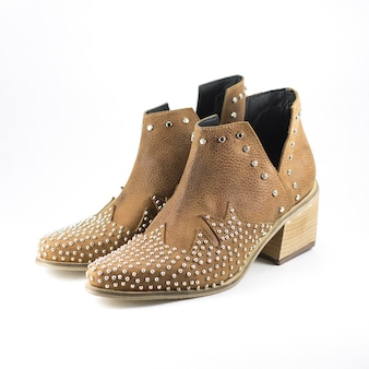 Closeup of leather high-heeled female brown shoes decorated with metal parts