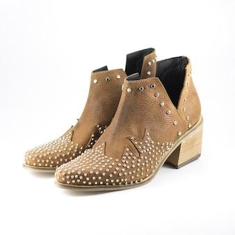 Primo piano delle scarpe marroni femminili a tacco alto in pelle decorate con parti metalliche