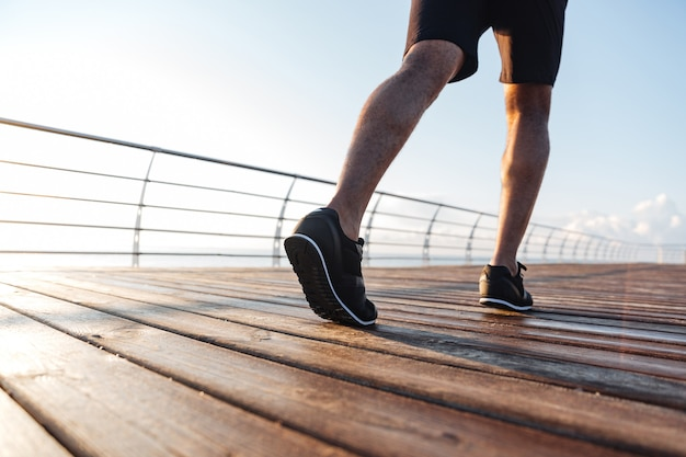 Closeup of legs of african american young man in black sneakers running on wooden terrace