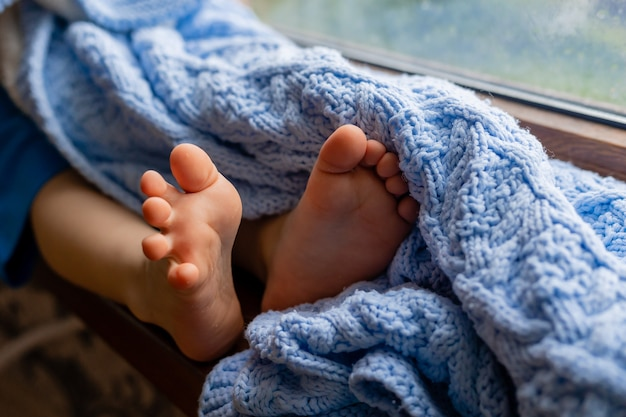 Closeup of the legs of a sitting child with bare feet covered with a blue knitted blanket lifestyle