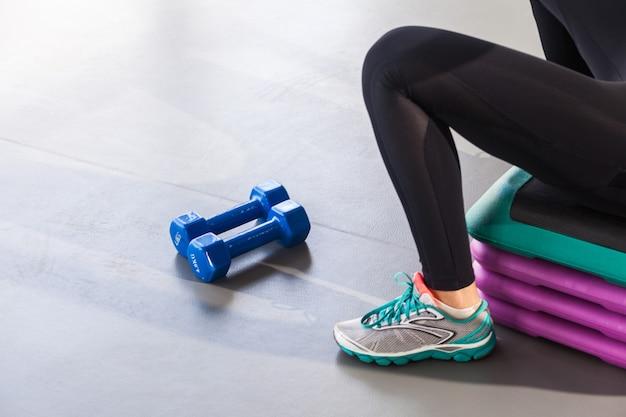 Крупным планом ноги кроссовки шаг платформы и гантели женщина сидит