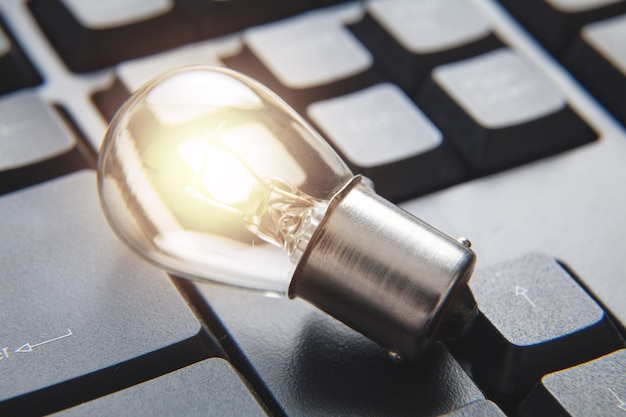Closeup of light bulb on computer keyboard