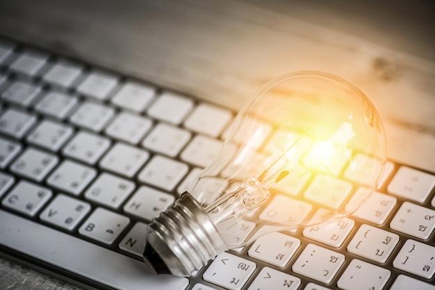 Closeup light bulb on keyboard laptop, new ideas, innovation, inspiration and creativity c