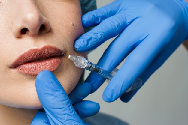 Closeup lips augmentation injections for attractive girl