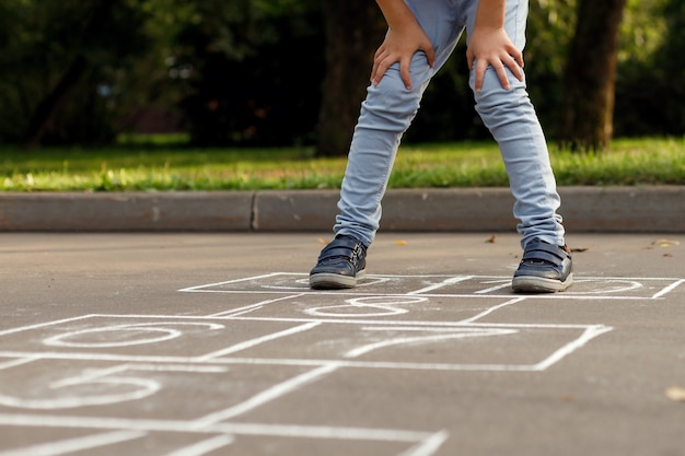 Closeup of little boy's legs and hopscotch drawn on asphalt. child playing hopscotch game on playground outdoors.