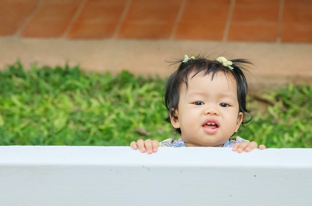 Closeup little girl catch a white fence on grass floor in the garden background with smile face