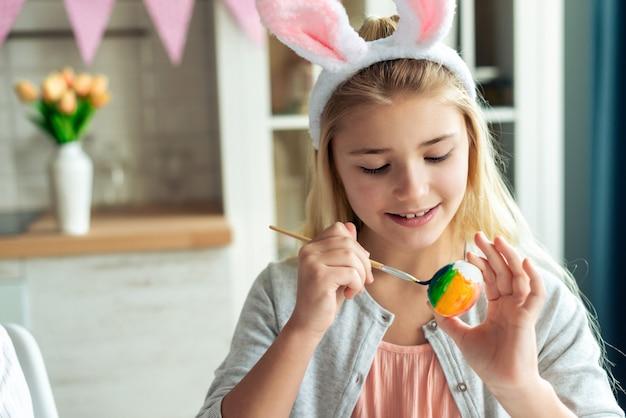 근접 촬영 어린 소녀는 부활절 달걀을 그립니다.