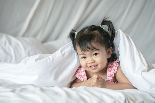Closeup a little girl lie on bed under blanket with smile face in the morning