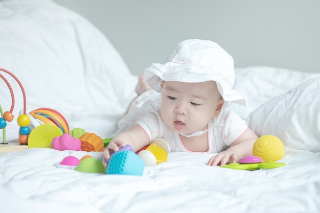 Closeup little girl play toy on bed Premium Photo