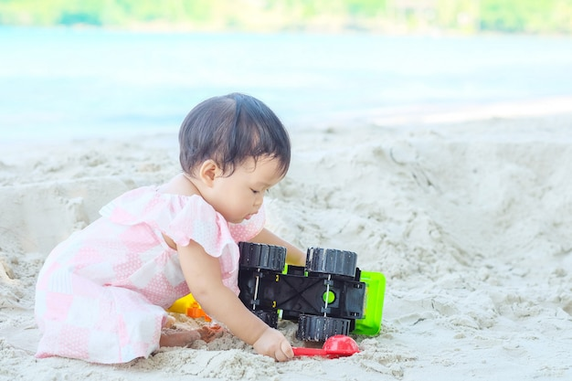 Closeup little girl play with sand and toy on beach textured background with copy space