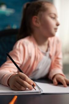 Primo piano di una piccola studentessa che studia lezione online lavorando a compiti di matematica
