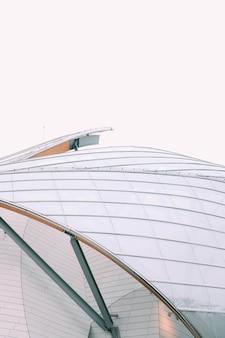 회색 하늘 아래 흰색 유리 창문이있는 현대적인 건물의 근접 촬영 모습