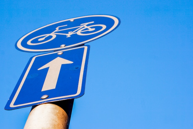 Closeup and look up view traffic signs of bicycle lane and navigation arrow on clear blue sky background.