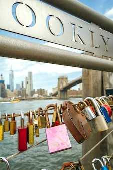 Closeup of love locks in fence with brooklyn bridge of new york city on the background