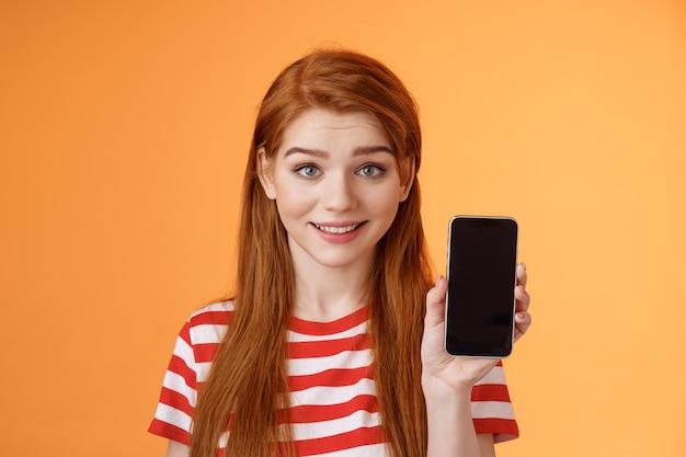 Крупным планом милая кавказская рыжая девушка показывает экран смартфона на оранжевом фоне, улыбаясь мило реком ...