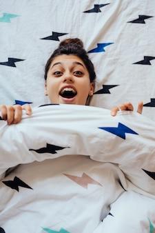 Primo piano di bella giovane donna si trova a letto coperto di coperta.