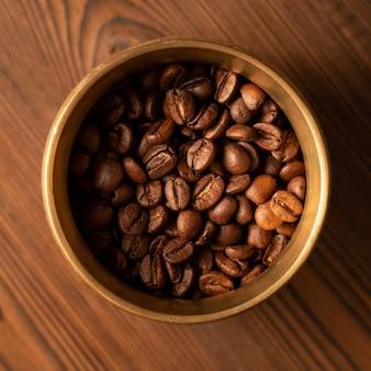 Жареные кофейные зерна (арабика) в металлической чашке. вид сверху. closeup. macro.
