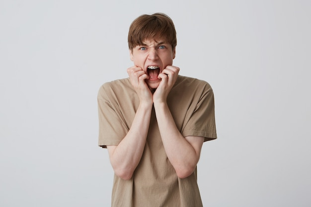 Closeup of mad crazy young man with braces on teeth and opened mouth wears beige t shirt looks aggressive and shouting over white wall