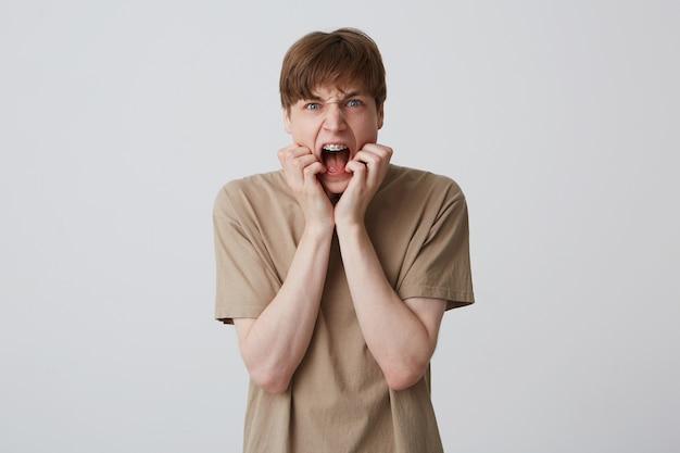 Il primo piano del giovane pazzo pazzo con le parentesi graffe sui denti e la bocca aperta indossa la maglietta beige sembra aggressivo e gridando sopra il muro bianco
