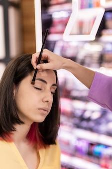 Макрофотография визажист наносит косметику по уходу за кожей латиноамериканской женщине в салоне красоты образ жизни лица и руки, наносящей макияж кистью желтый цвет года