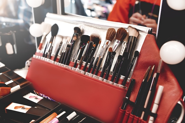 Closeup of makeup tools. professional makeup brushes in tube, leather bag on a wooden table.