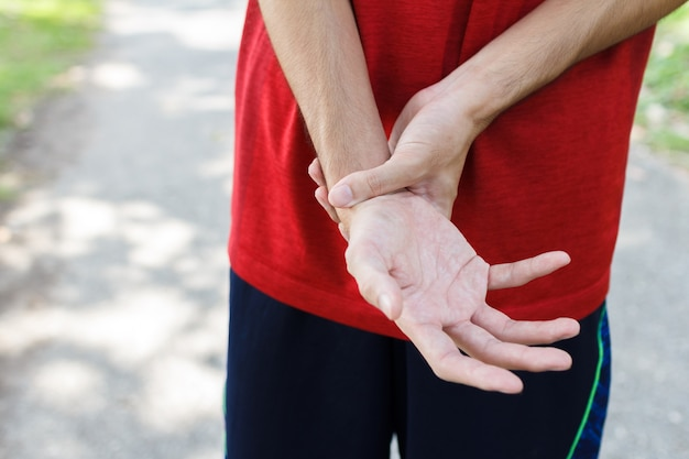 Closeup of male arms holding her painful wrist because exercise