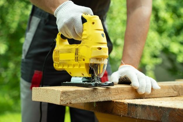 Плотник крупным планом режет деревянную доску с помощью электрического лобзика