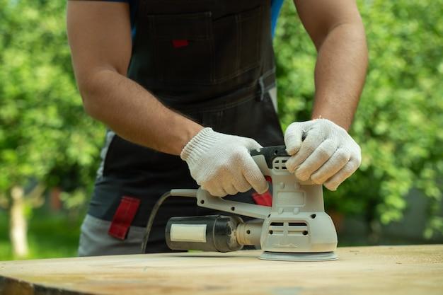 Плотник крупным планом полирует деревянный стол на шлифовальном станке