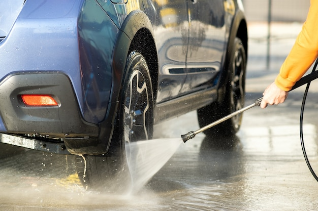 Closeup of male driver washing his car with contactless high pressure water jet in self service car wash.
