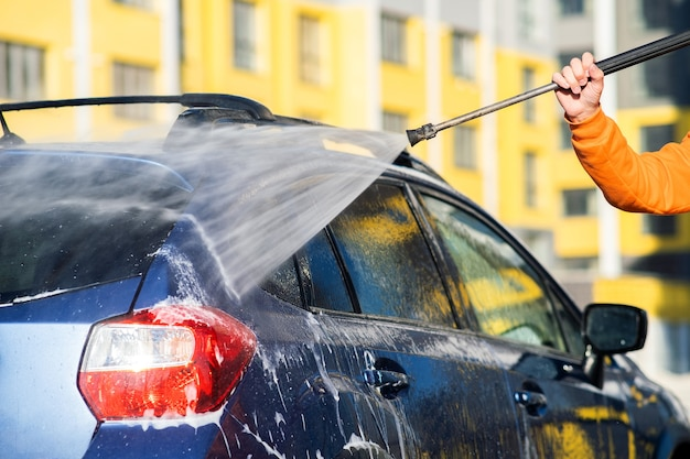 Closeup of male driver washing his car with contactless high pressure water jet