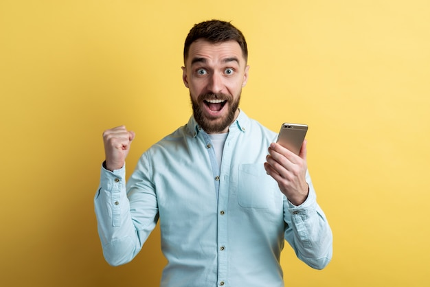 Closeup male face holding a smartphone and excited looking clenching a fist in win pose. emotion winner