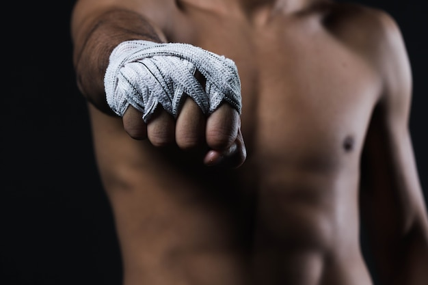 Closeup male fighter hand with bandages. fighter's fists clenched before a fight or training in a sports gym.