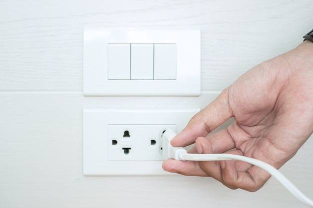 Closeup male finger unplugging or plugging of electricity device on white wall at home.