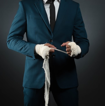 Closeup male hand of businessman fighter in suit with bandages and clenched fists.