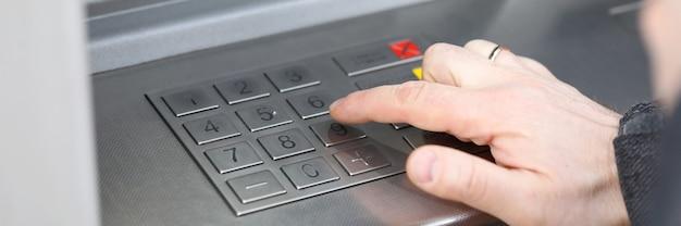 クローズアップ男性の手は、ターミナルのピンコードをダイヤルします。銀行設備。 atm詐欺の範囲。現金引き出しのための安全なパスワード入力。 atmは詐欺師によってハッキングされました。スマートフォンを充電してください。カード残高