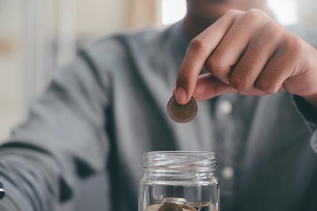 ガラスに入れてコインを持っている男性の手のクローズアップ。