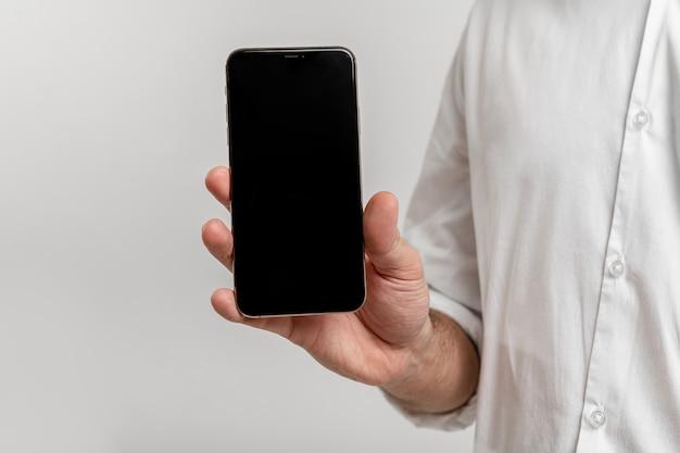 白いモックアップスマートフォンの空白の画面で隔離の電話を保持している男性のクローズアップ