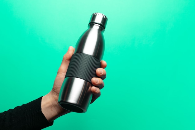 Closeup of male hand holding steel reusable bottle on green background.