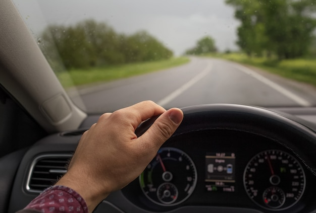 Closeup of male hand holding steering wheel, driving the car. background of blurred road in rainy day. transportation concept.